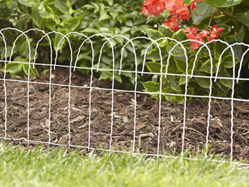 Ordinaire White Decorative Scroll Top Garden Border Fence Separates The Flower Bed  From The Lawn.