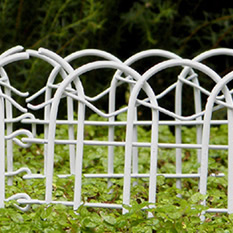 Several pieces of white fairy garden fence encircle to form a small space, stand on a large area which is full of green plants.