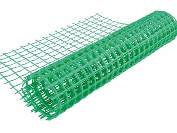A Roll Of Green Plastic Garden Fence With Some Unfolded Part Is Lying On  The White
