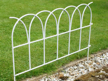 One piece of lawn edging fence is pushed into the rocky ground and separates the lawns from the pathway.