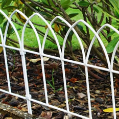 White peaked top garden fences connect together to protect the plants and lawns.