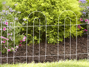 Four pieces of white garden border double round folding fence link together and blend beautiful into the landscape.
