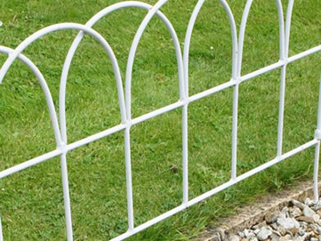 A part of the fence decorates and protects the lawn, and the fence is pushed into the rocky ground.
